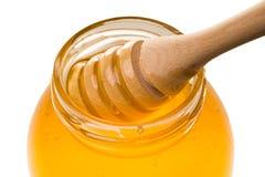 Pot en verre de miel avec le drizzler en bois d'isolement sur le backgr blanc photos libres de droits