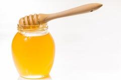 Pot en verre de miel avec le drizzler en bois d'isolement sur le backgr blanc image stock