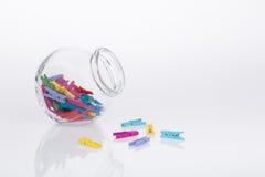 Pot en verre de pinces à linge miniatures colorées Images stock