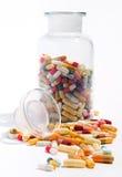 Pot en verre et un grand choix de capsules et de pilules Image stock