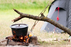Pot on fire. Camping kitchenware - pot on the fire at an outdoor campsite Royalty Free Stock Images