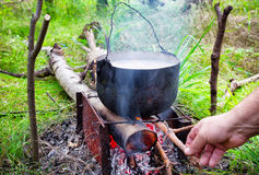 Pot on the fire with firewood tosses hand Stock Photography