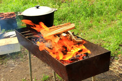 Pot on the fire grill. Pot water on the fire, tourists kettle on hot campfire. Camping photo Royalty Free Stock Photos