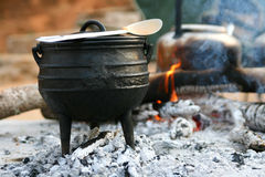 Pot on fireplace. Old pot on open fire Royalty Free Stock Photo