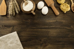Pot of flour, wheat ears, pasta, eggs, kitchen utensils on wooden background. Stock Photos