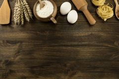 Pot of flour, wheat ears, pasta, kitchen utensils on wooden background. homemade, menu, recipe, mock up Stock Photography
