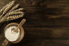 Pot of flour and wheat ears on wooden background. Stock Photography