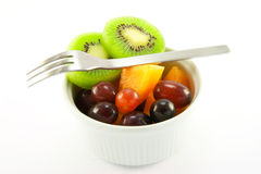 Pot of Fruit with Fork. Pot of fruit including kiwi, melon and grapeswith a  fork and clipping path on a white background Stock Photo