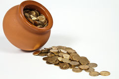 Pot full of gold coins. Clay pot with gold coins on a white background Stock Images