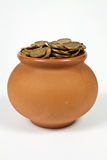 Pot full of gold coins. Clay pot with gold coins on a white background Stock Photo