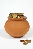 Pot full of gold coins. Clay pot with gold coins on a white background Royalty Free Stock Photo