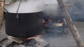 Pot fumigène noir chaud sur l'eau bouillante du feu, préparant la soupe ou le thé dans une foire de ville Bois de chauffage brûla banque de vidéos