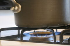Pot on Gas Stove. Metal pot cooking on gas stove over blue open flame Stock Photography