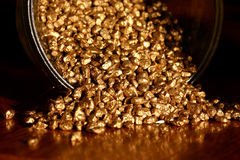 Pot of gold. Small gold granules stock photography