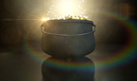 Pot Of Gold. A cast iron pot filled with gold coins and magical sparkles on a dark eerie spotlit background royalty free stock image