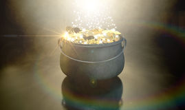 Pot Of Gold. A cast iron pot filled with gold coins and magical sparkles on a dark eerie spotlit  background Royalty Free Stock Photography