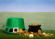 Pot of gold in grass next to a leprechaun hat stock image