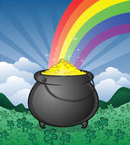 Pot of gold with rainbow in clover patch. A pot of gold with a rainbow set in a full clover patch with mountains and sky Royalty Free Stock Photography