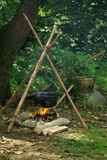 Pot hanging over campfire. A cook pot hanging over a wood campfire, heating water or food stock photo
