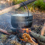 Pot hanging over the fire. In the forest in a hike, the water vapor from the boiler stock image