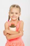 Pot heureux d'étreinte de petite fille de cactus Photographie stock libre de droits