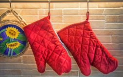 Two red potholders and trivet hanging in a modern classic cuisine. A pair of oven gloves hanging on kitchen bars Royalty Free Stock Image