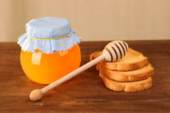 Pot of honey and rusks Stock Photos