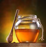 Pot of honey and wooden stick. Royalty Free Stock Photos