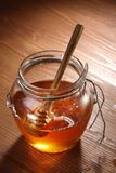 Pot of honey and wooden stick in it. Royalty Free Stock Image