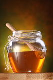 Pot of honey and wooden stick in it Stock Photo