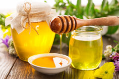 Pot of honey and wooden stick Royalty Free Stock Image