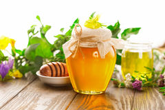 Pot of honey and wooden stick Stock Photos