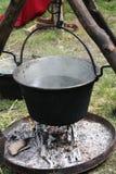 Pot médiéval antique avec de l'eau sur le feu et les trépieds au suppo image libre de droits