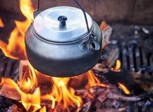 Pot métallique de café dans la chaleur de feu de camp Photo libre de droits