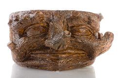 Pot made of clay in the shape of the face in tree trunks on whit. E background Stock Photos