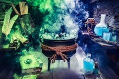 Pot magique de sorcière avec des livres, des rouleaux et des breuvages magiques photo stock
