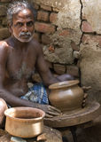 Pot maker at his turning table with finished product. Stock Photo