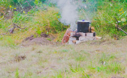 The pot of meal is on the rocks and fire. The trek food is cooked on the fire and the pot stands on the stones Stock Image