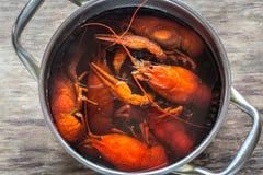 Pot met gekookte rivierkreeften op de houten lijst Stock Foto