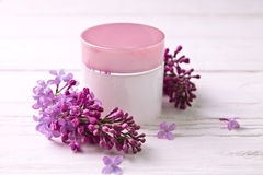 Pot of moisturizing cream with lilac flowers royalty free stock photos