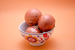 Pot with onions. Close-up on a background color Stock Images