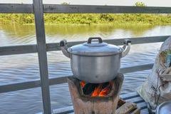 Pot op een houtskoolfornuis stock afbeelding