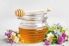 Pot organique cru de miel avec des fleurs images stock