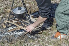 Cooking on a fire at spring. Close view of caldron over the campfire. Pot over the fire in the forest. Cooking on a fire. Spring camping concept. Man`s hand puts royalty free stock image
