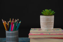 Pot plant, color pencils and book stack on wooden table. Against black background Royalty Free Stock Image