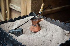 Pot for preparation of turkish coffee on hot sand Royalty Free Stock Photography