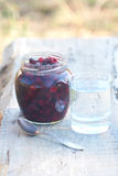 Pot with preserve and tumbler with transparent water Royalty Free Stock Image