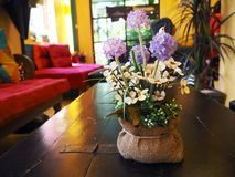 A pot put on wooden table in yellow room. Flowers color are violet, purple, and white with green leaves. Red sofa in the room. No. People. A room is boutique stock images