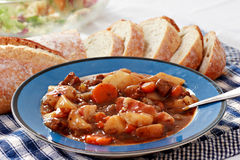 Pot Roast Dinner. A bowl full of beef pot roast with bread and salad Royalty Free Stock Photography