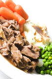Pot roast dinner potatoes carrots green peas Stock Photo